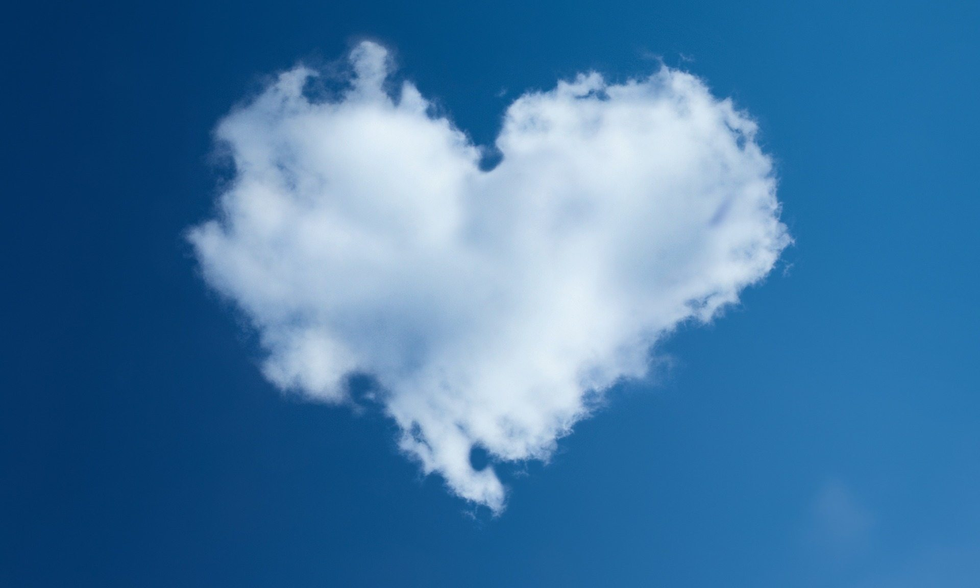 Image: A brilliant blue sky with a fluffy heart-shaped cloud in the middle