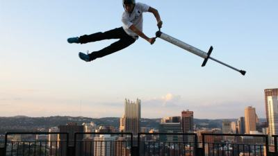 Image: pogo stick rider in the air above the city
