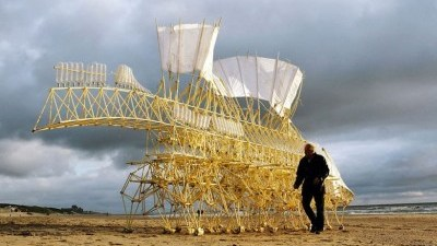 Image: Theo Jansen on the beach with a Strandbeest, a large mechanical sculpture