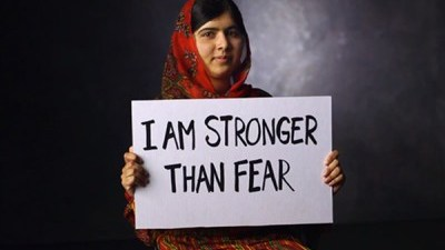 "Image: Malala poses with sign that reads ""I am stronger than fear"""