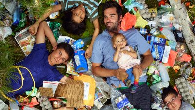 Image: a family laying in their weeks worth of garbage