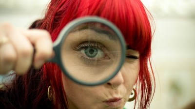 Image: Red-haired woman looks into magnifying glass