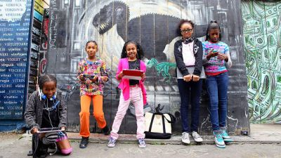 Image: Girls hold electronic devices as they learn coding