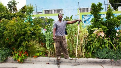 Image: Ron Finley standing on the curb of a street-side garden holding some key gardening essentials