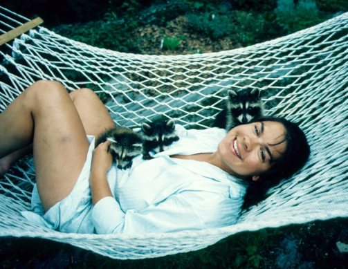 Image: Dr. Lynda with three baby raccoons she raised as a teenager