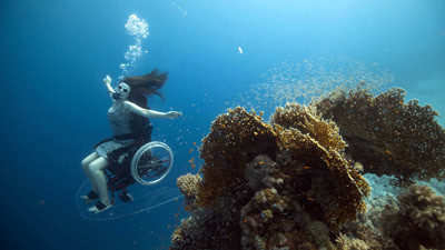 Image: Woman diving with underwater wheelchair