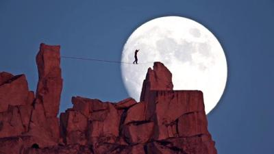 Dean Potter Rope Walking Over Rocks With Moon Behind