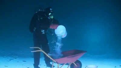 Image: Diver standing on ice under water