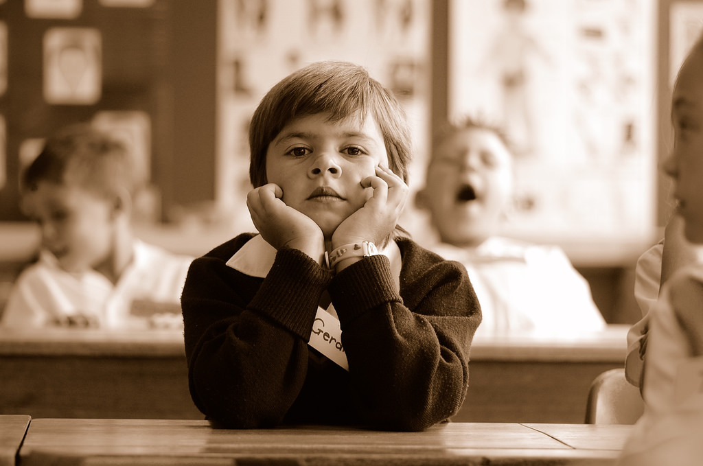 Image: A boy bored at school, do schools kill creativity?