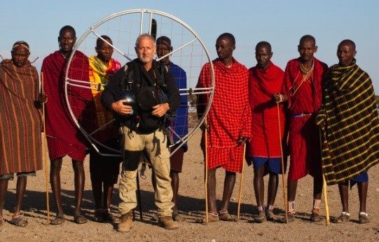 Image: Theo with paraglider on his back with Tribesmen