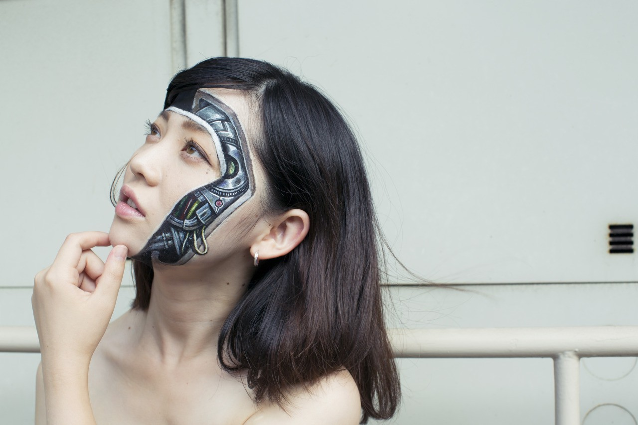 Image: Woman's face looks like she is removing it to reveal a machine by Hikaru Cho