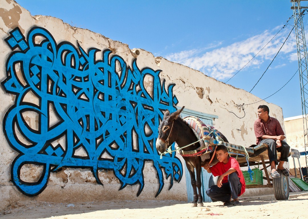 Image: el Seed caligraffiti on a wall with donkey cart in front of it