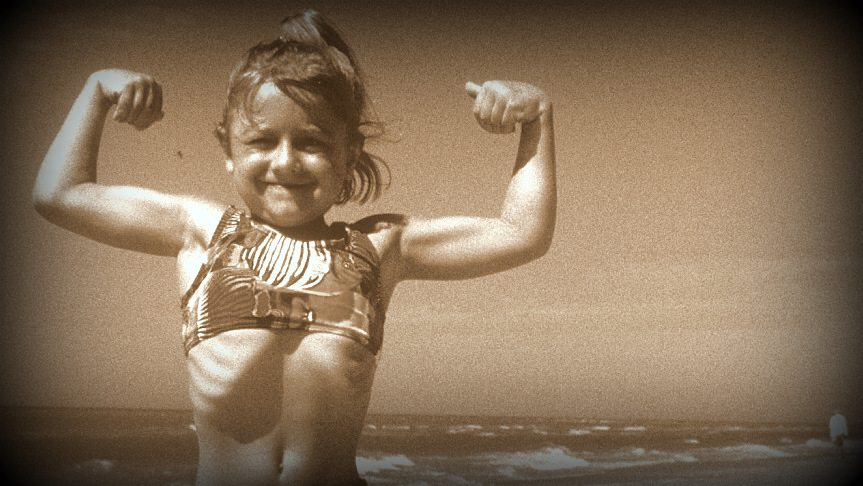 Image: Little girl making muscles on a beach