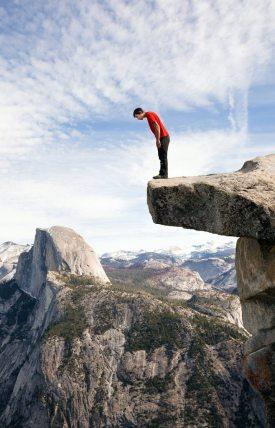 Image: Alex Honnold climbing concrete jungles on rock ledge.