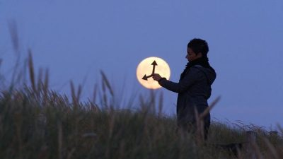 Image: Man setting back time on a clock that is the moon rising