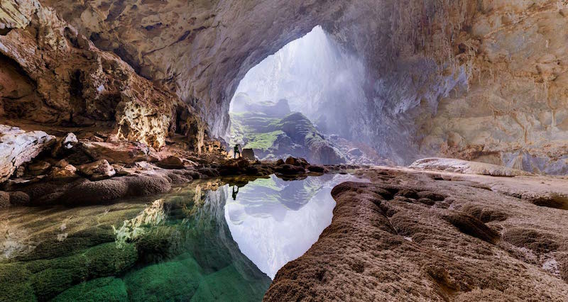 Image: Hang Son Doong Cave entrance to cave Rainforest with a person standing above a water pool