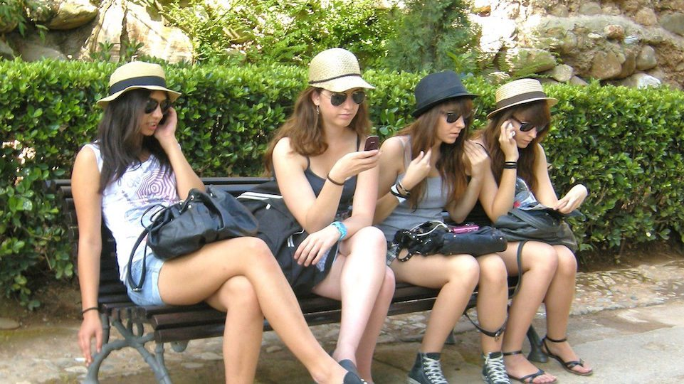 Image: Girls sitting on a bench on their cellphones