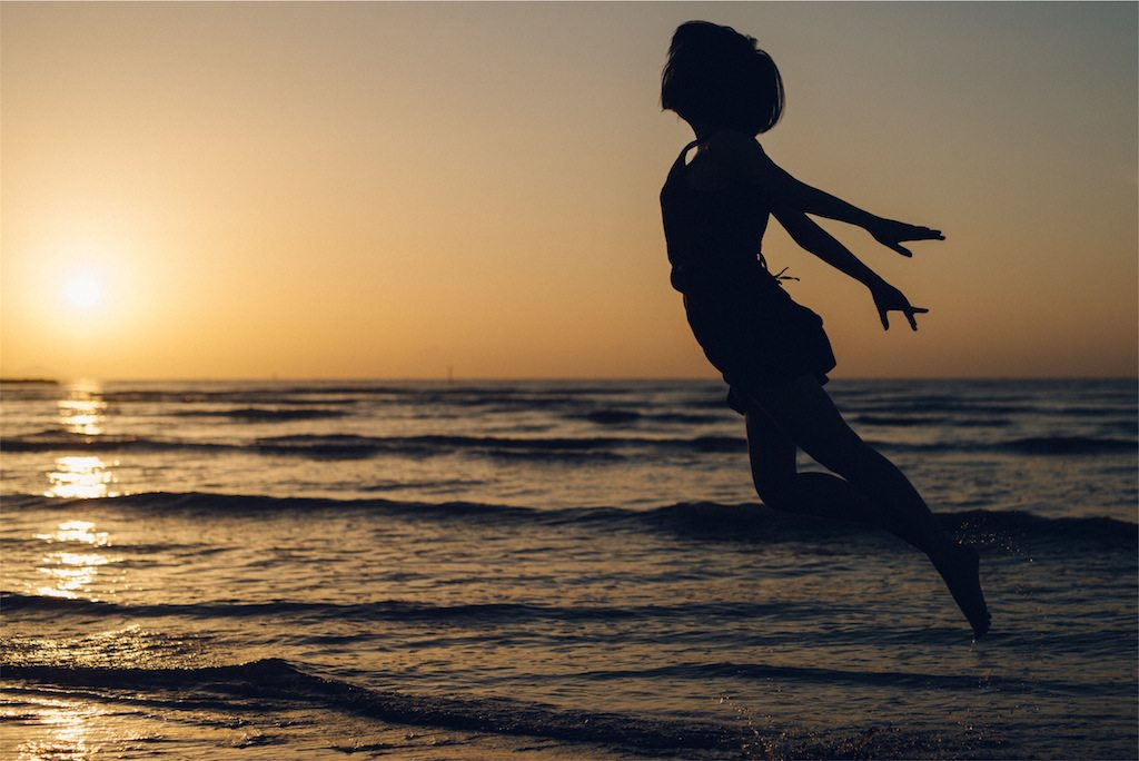 Image: Silhouette of a person against and ocean sunset appearing to fly
