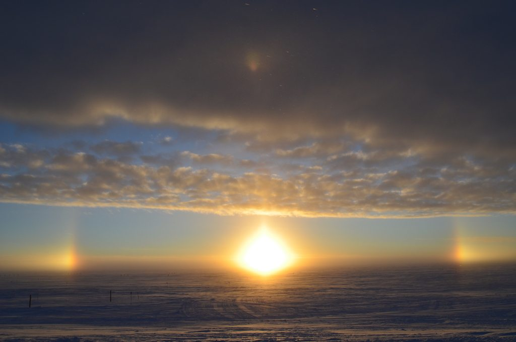 Image: A sundog sunset, with the sun setting and a halo of light surrounding it.