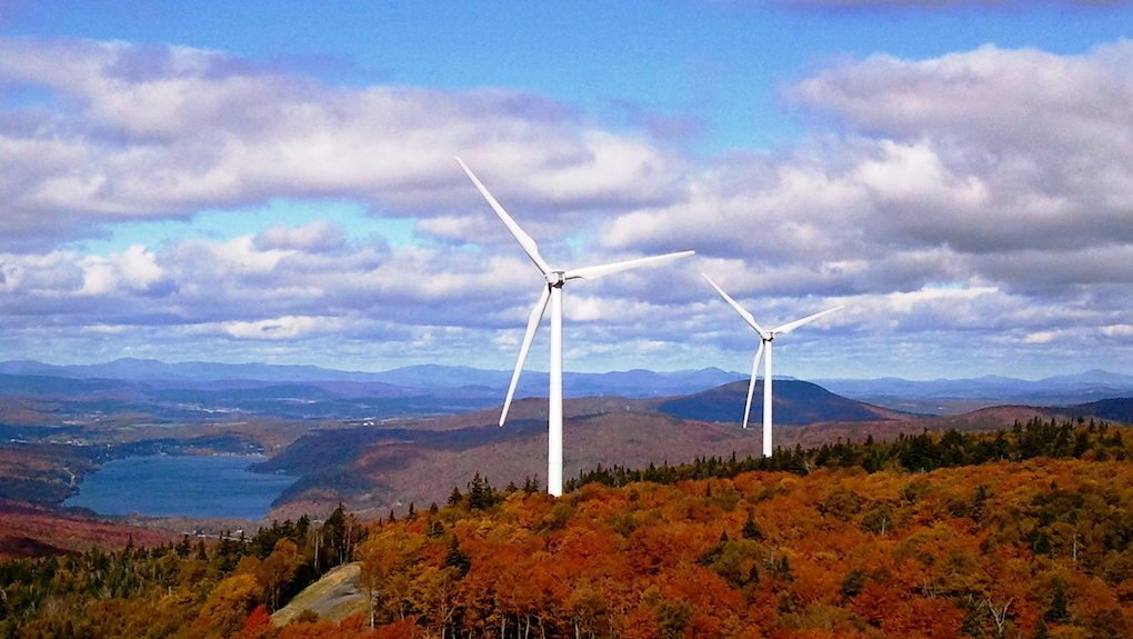 Image: Wind turbines on a hill covered with fall foliage