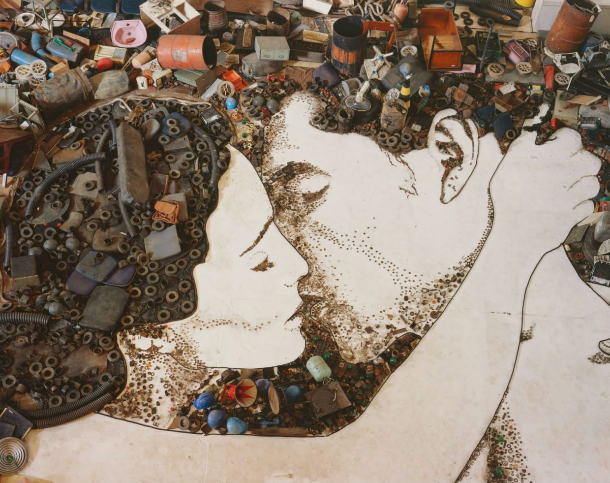 Image: Garbage laid out on the floor to make a huge image of people kissing