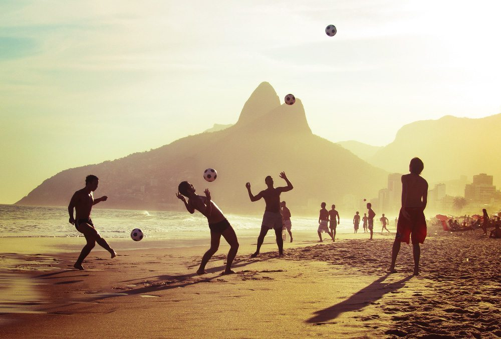 Image: People playing soccer and finding joy in the beautiful game on the beach with the mountains and sun behind them