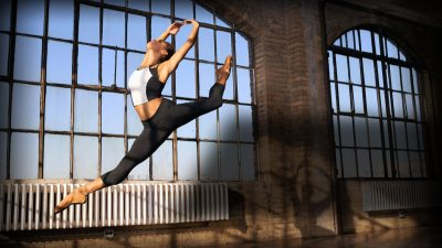 Image: Ballerina Misty Copeland in a beautiful leap in front of a warehouse window