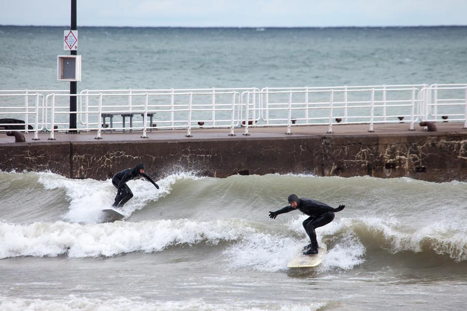 Image: Great Lakes surfers surfing by a pier.