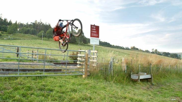 Image: Stunt Cyclist Danny MacAskill jumping a farm fence