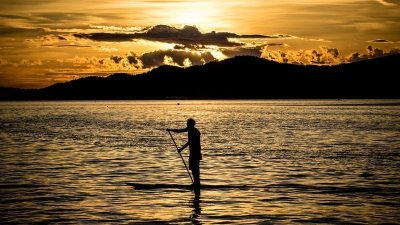 Image: Man on a paddleboard out in the ocean at sunset