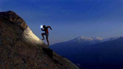 Image: man running up a mountain at dusk with a headlamp