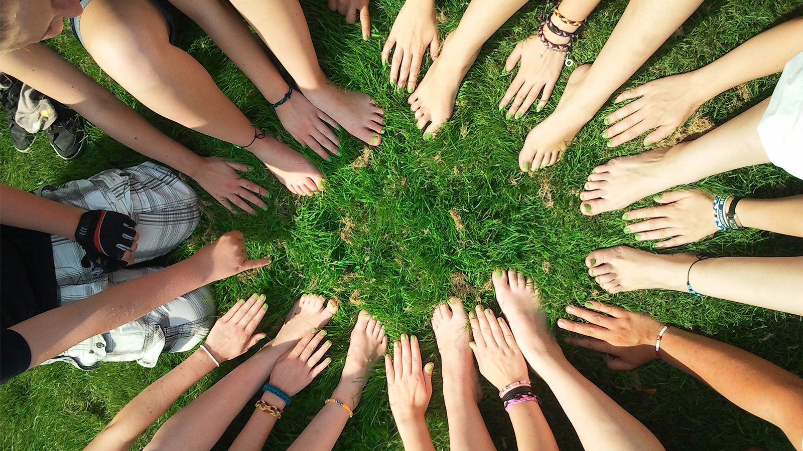 Image: people placing their hands and feet in a circle