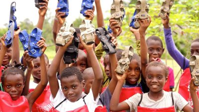 Image: Children holding pairs of The Shoe that Grows