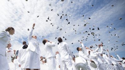 Image: Coast Guard Graduates in white suits toss their hats in the air