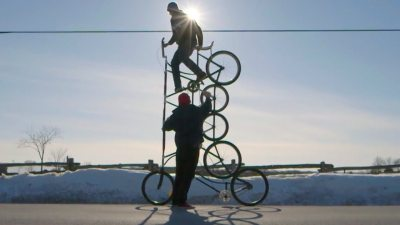 "Image: A person riding one of many ""Tall Bikes"" that is 5 wheels tall."