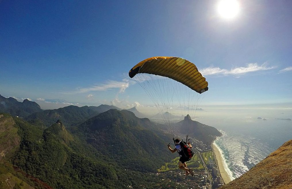 Image: Person lifting off into the air over a gorgeous mountain range using their speedfly gear
