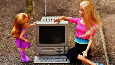 Image: two blonde female barbies, one adult and one child, sitting down next to an old desktop computer. The older barbie appears to be explaining the machine to her.