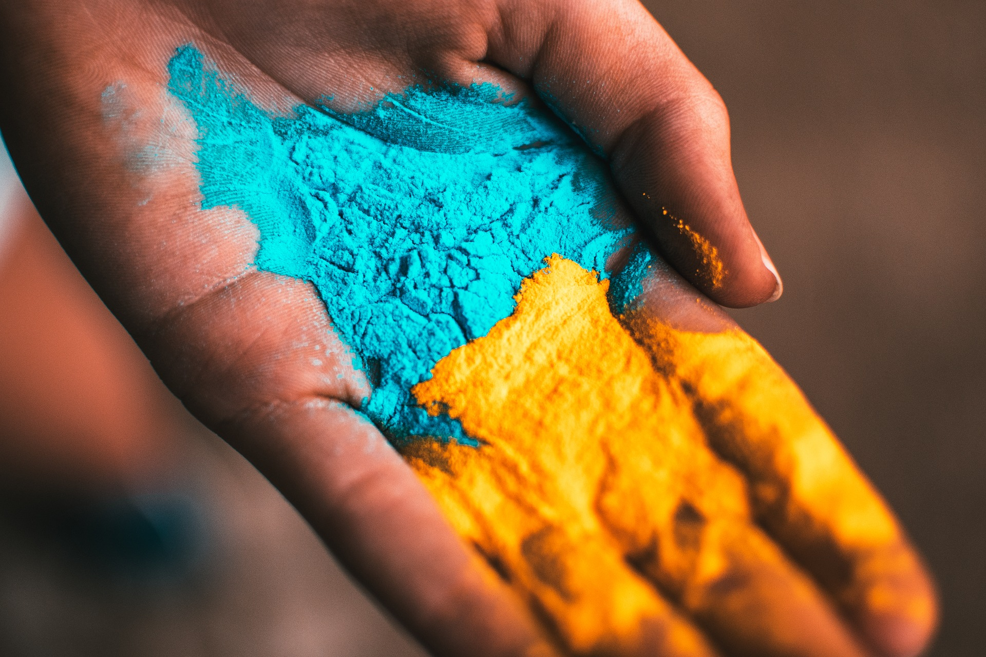 Image: hand holding yellow and blue pigment powder, this pigment works similarly to the color of our skin