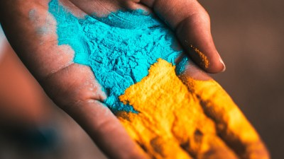 Image: hand holding yellow and blue pigment powder