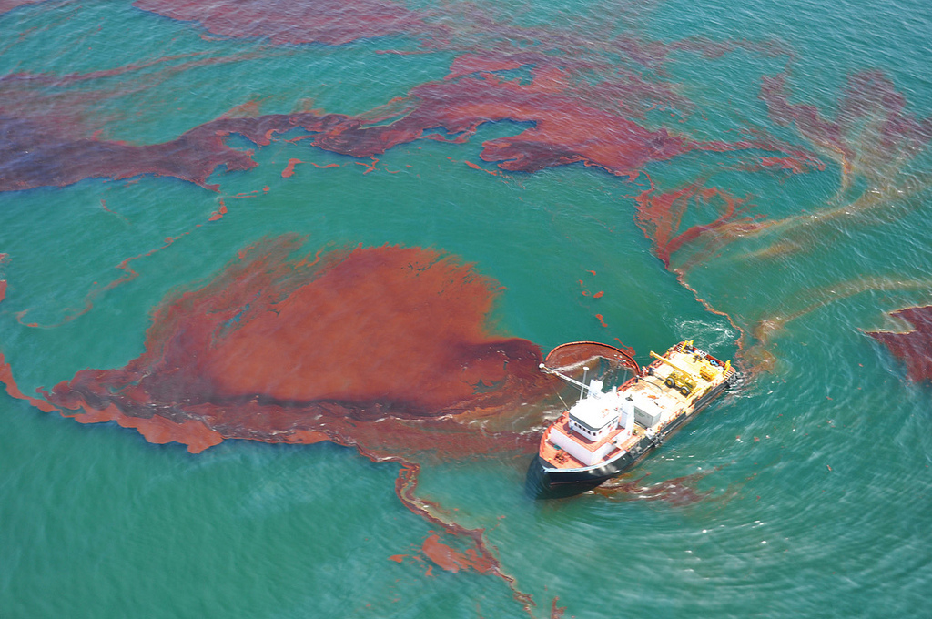 Image: rust colored oil in clear aqua blue water with a boat working to skim oil