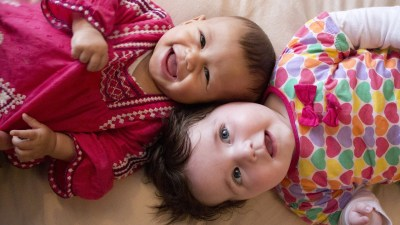 Image: Two babies talking and smiling at camera