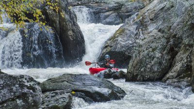 Image: Person kayaking through some rocks