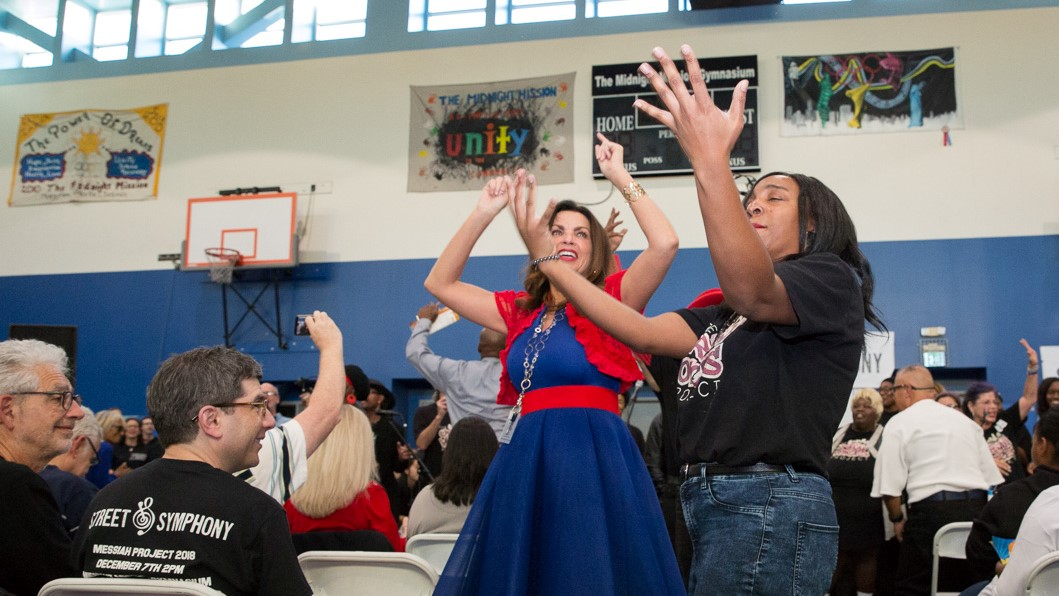 Image: people dancing in a gymnasium during the Street Symphony production of The Messiah Project