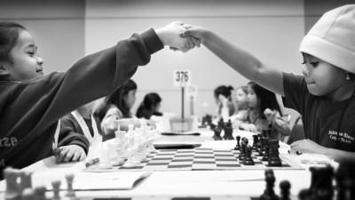 Image: Girls shaking hands over a chess game