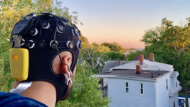 Image: A man wearing the headset and staring out into the distance at a sunset