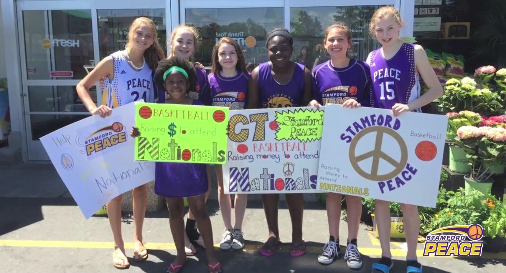 Image: Girls on the Stamford Basketball team standing with smiles and inspiring posters.
