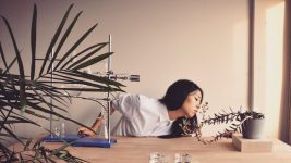 Image: Framed shot of Ani Liu leaning over to smell a plant