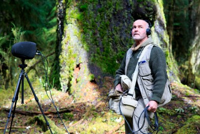Image: Gordon Hempton staring off into the Hoh Rainforest wearing headphones with a recording apparatus in front of him