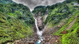 Image: Large waterfall running between two green mountains