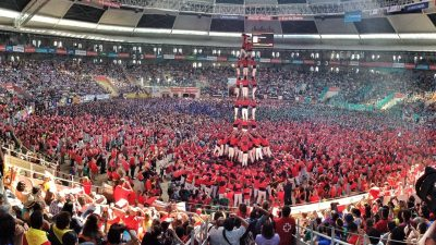 Image: a crowd of people watch as people build a human tower called a Castell